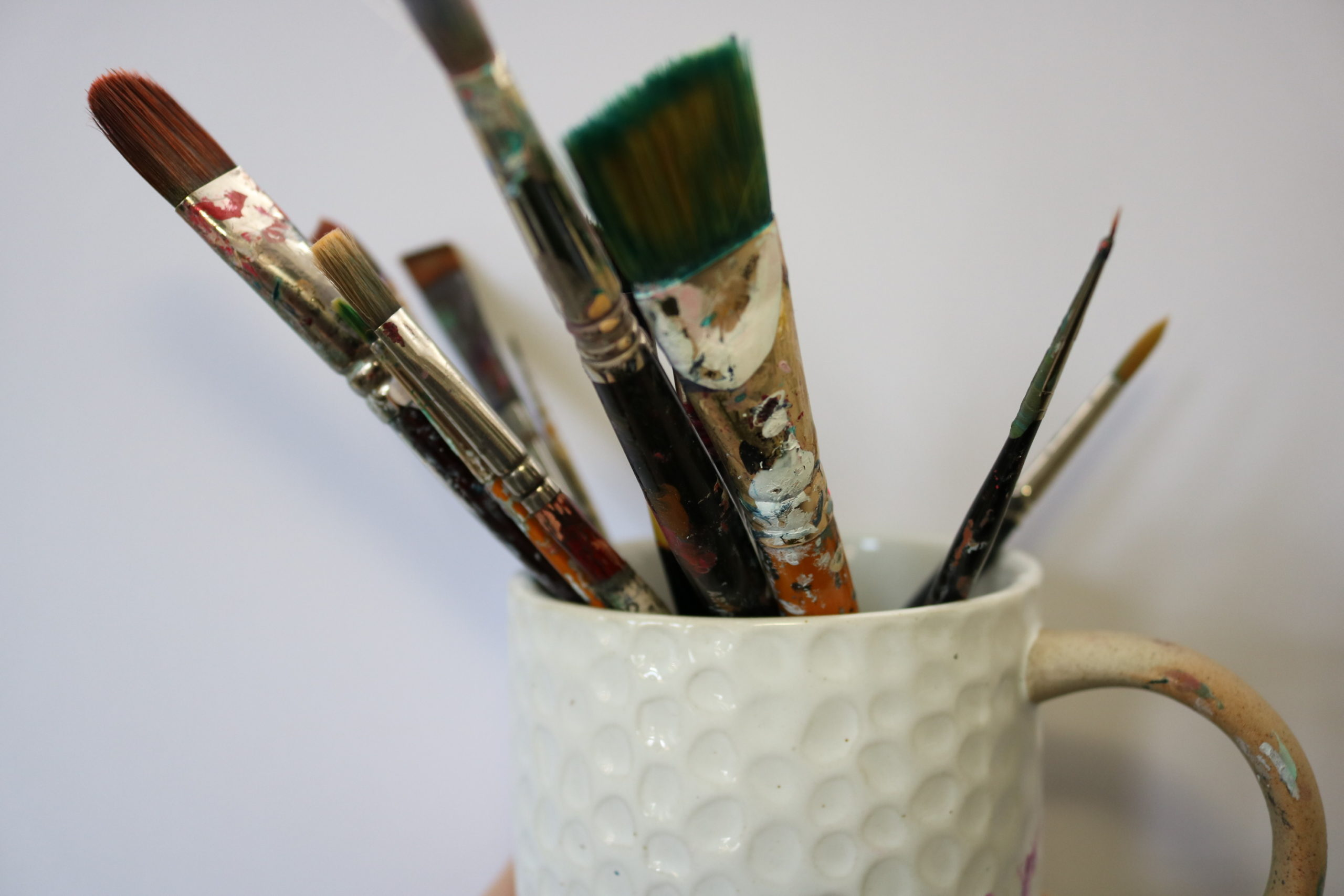 paint brushes in coffee mug